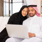 lovely arabian couple using laptop at home